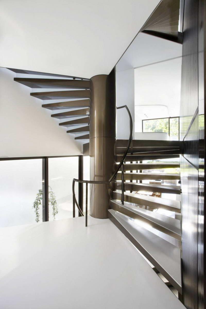 Эффектная винтовая металлическая лестница, с белоснежными ступенями из дерева.
