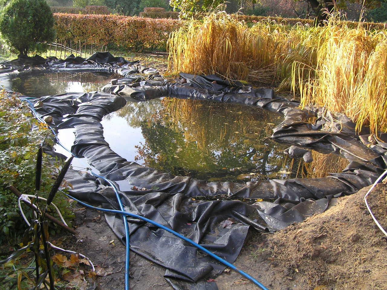 Постепенно геомембрана принимает форму водоема, и ее складки, образующиеся в процессе укладки, под давлением слоя воды становятся незаметны.