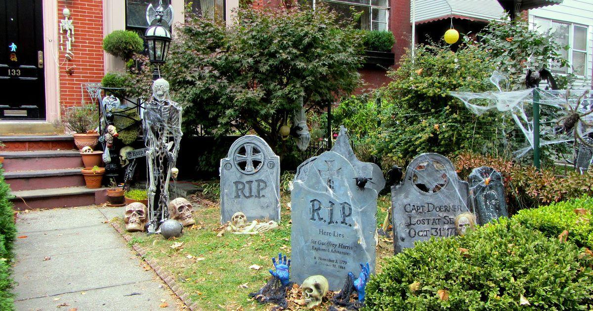 Скелет и надгробие в саду на Хеллоуин