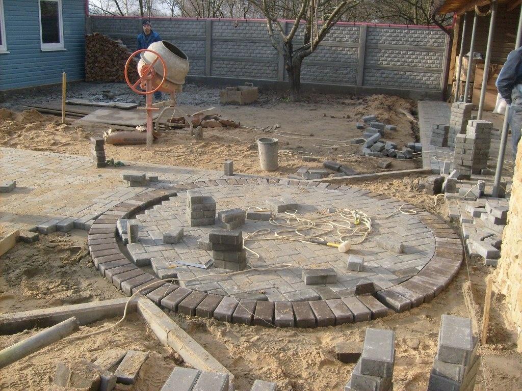 Мощение начинаем от центра площадки к краям. При мощении следите, чтобы плитка или брусчатка выступала не менее чем на 3 см выше уровня песка.