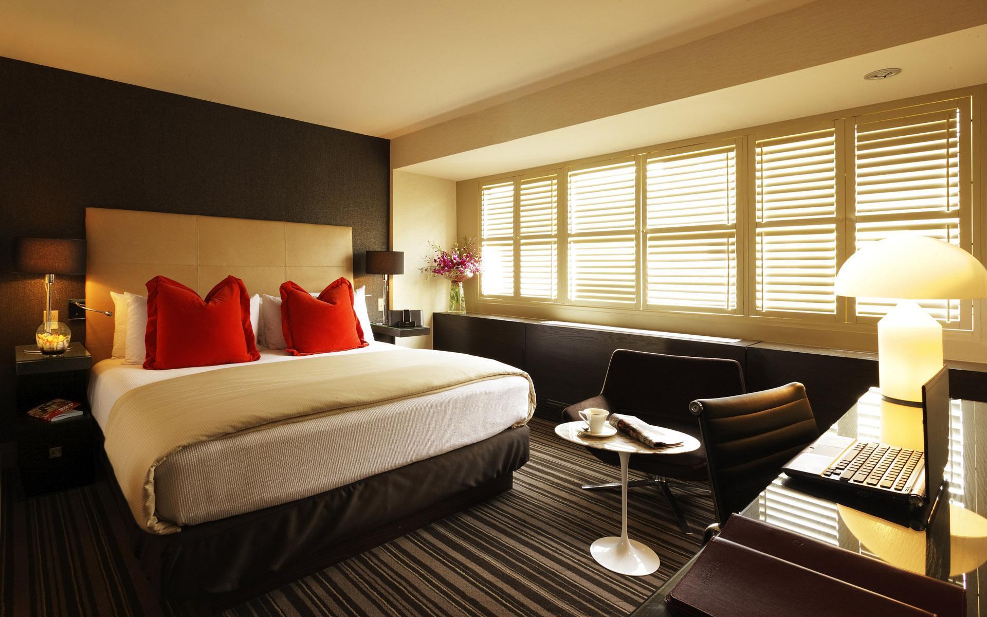 Минимум мебели и скрытые ниши, встроенные шкафы и большие окна помогают сделать спальню просторной.