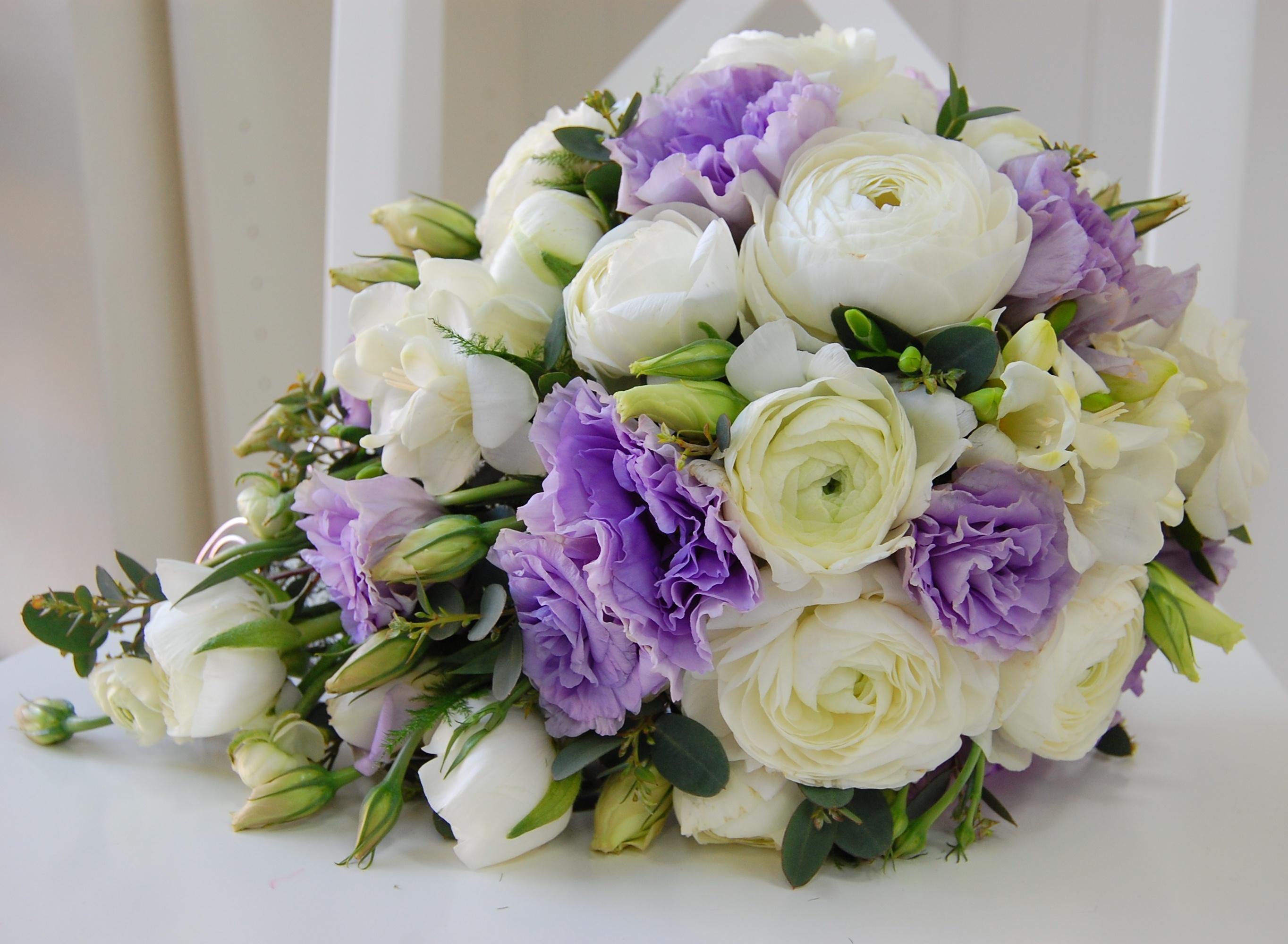 Букет цветов составляют: белоснежные ранункулюсы, белая фрезия теплого оттенка, сиреневая эустома, эвкалипт, аспарагус.