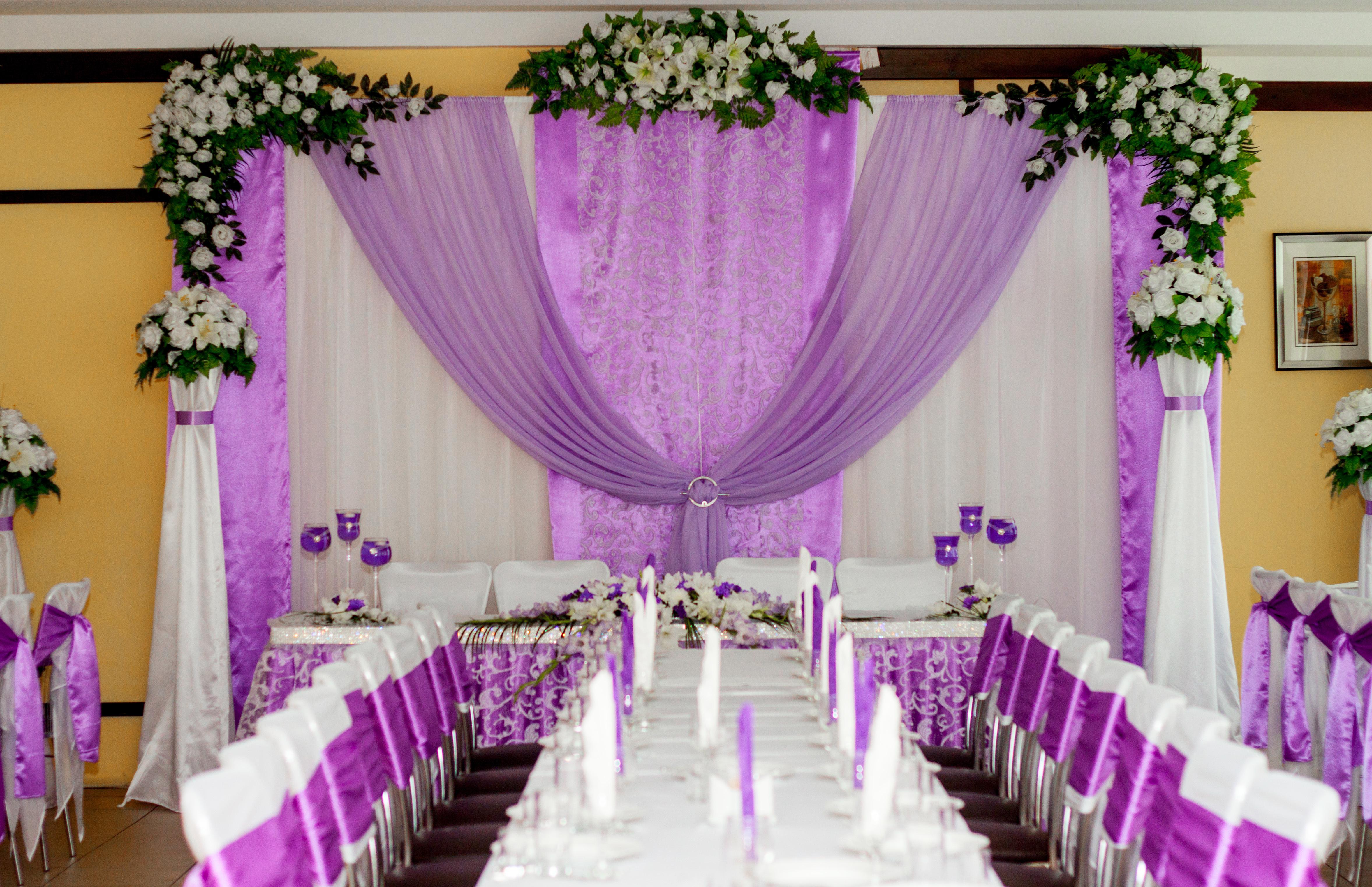 Изысканно выглядит место за столом молодых, задекорированное шторой из живых цветов и нитей из бусин.
