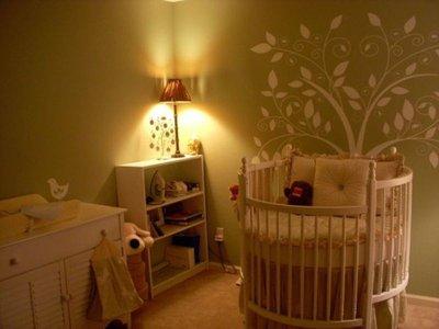 Комната для новорожденного. Симпатичное стилизованное деревце на стене возле кроватки крохи
