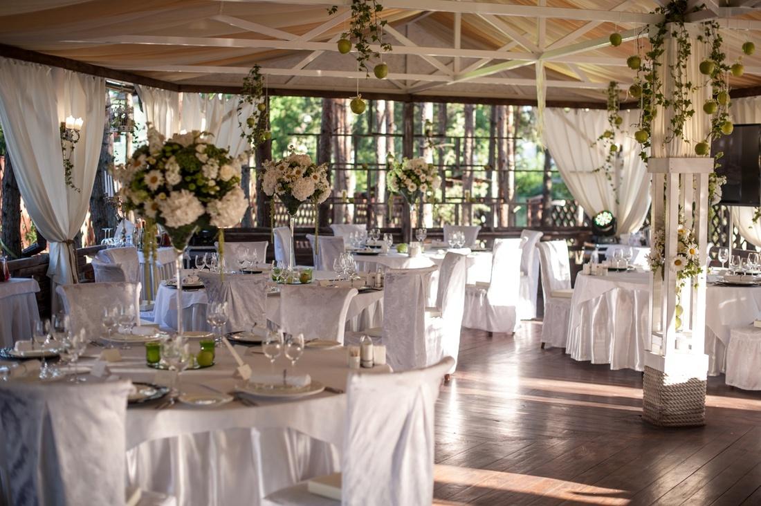 """Цветочные композиции на столы гостей могут быть со свечами в вазах на длинных ножках в стиле """"мартини"""""""